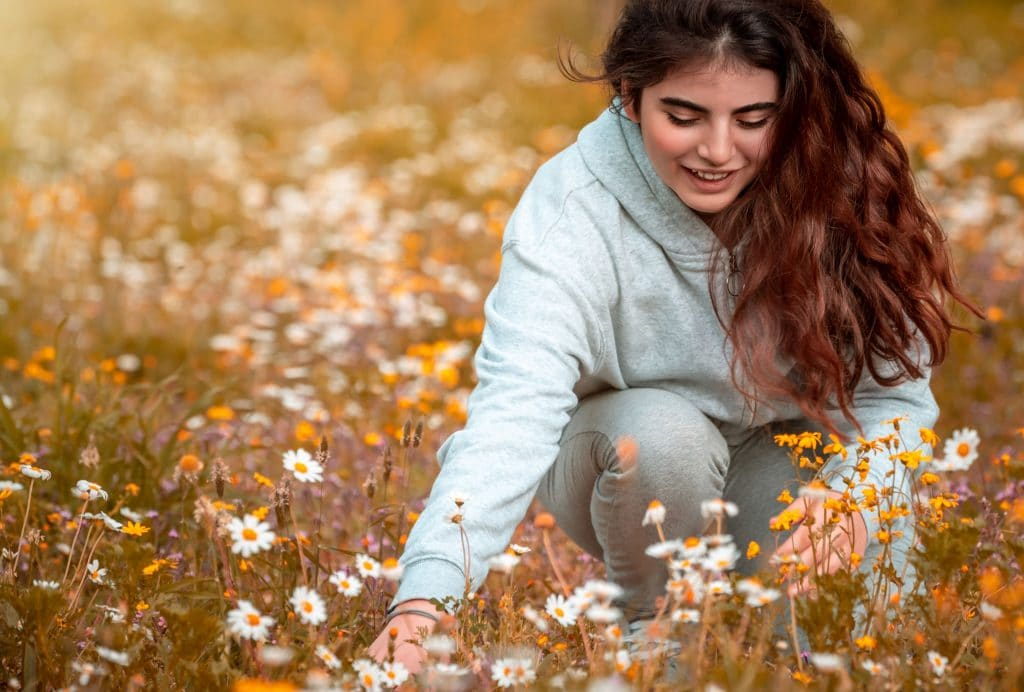 teen girl picking flowers